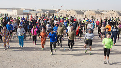 © London News Pictures. 01/01/2014. Members of the Armed Forces take part in a New Years Day fun run in Camp Bastion, Afghanistan. 2014 will mark the final year of operations in Helmand Province as some of the 5,000 soldiers prepare to come home. Photo credit: Alison Baskerville/LNP