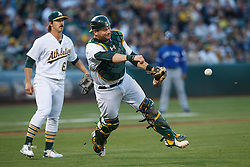 OAKLAND, CA - JULY 15:  Stephen Vogt #21 of the Oakland Athletics commits a throwing error after fielding a ground ball against the Toronto Blue Jays during the first inning at the Oakland Coliseum on July 15, 2016 in Oakland, California. (Photo by Jason O. Watson/Getty Images) *** Local Caption *** Stephen Vogt