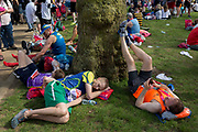 Tired long-distance runners rest after finishing the London Marathon, in St James's Park, on 22nd April 2018, in London, England.
