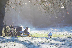 © Licensed to London News Pictures. 18/01/2018. London, UK. A woman takes a break while walking her dog on a frosty Hampstead Heath. Photo credit: Rob Pinney/LNP
