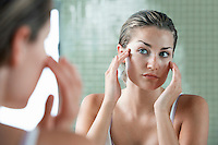 Woman rubbing temples in front of mirror