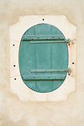 a round window with closed shutter set in an renovated old wall