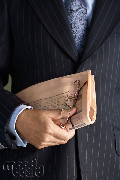 Middle-aged businessman in full suit holding pair of glasses and newspaper  mid section