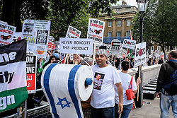 Pro-Palestinian protester holds a large roll of Israeli toilet paper as part of a demonstration outside Downing street against arms sales to Israel. London Aug 2014