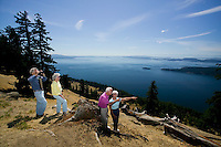 Sightseer's on the summit of Mt. Warburton Pike the highest peak on Saturna Island overlook Boundary Pass towards the San Juan Islands in the U.S.A.  Saturna Island, Gulf Island, British Columbia, Canada.