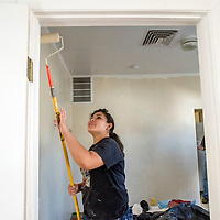 Skills USA participant Crystal Diaz brandishes a roller to paint an apartment doorway at the Battered Families Services center in Gallup Sunday.
