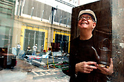 9/04/02--Rob Williams, owner of gallery W.D.O., is moving his art gallery to the new Hearst Plaza. While holding a teapot by artist Terry Gess, Williams, pictured inside his gallery, looks out through the window at the Hearst Plaza construction.  WENDY YANG/STAFF PHOTO