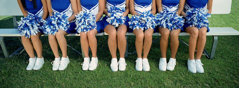 Group of cheerleaders sitting in row on bench, low section