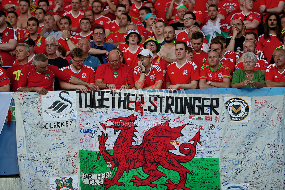 "TOULOUSE, FRANCE - Monday, June 20, 2016: Wales supporters' banner ""Together. Stronger Many tribes one nation"" featuring the badges of Swansea City, Newport County, Wrexham and Cardiff City during the final Group B UEFA Euro 2016 Championship match against Russia at Stadium de Toulouse. (Pic by David Rawcliffe/Propaganda)"