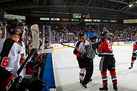 KELOWNA, BC - NOVEMBER 8:  Linesman Cody Wanner gets between Cole Clayton #34 of the Medicine Hat Tigers and Mark Liwiski #9 of the Kelowna Rockets during first period resulting in both players in the penalty box for roughing at Prospera Place on November 8, 2019 in Kelowna, Canada. (Photo by Marissa Baecker/Shoot the Breeze)