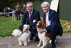 London, October 23rd 2014. Organised by the Dogs Trust and the Kennel Club, politicians  and their pooches gather outside Parliament for the 22nd Westminster Dog of the Year competition, aimed at raising awareness of dog welfare in the UK where the Dogs Trust cares for over 16,000 stray and abandoned dogs annually. PICTURED: Michael Gove and Andrew Mitchel pose with their dogs Snowy (left) and Scarlet.