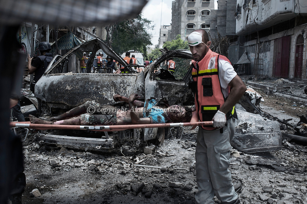 Gaza Strip, Gaza City: Medics evacuate the body of a boy from Gaza's eastern Shejaiya district. ALESSIO ROMENZI