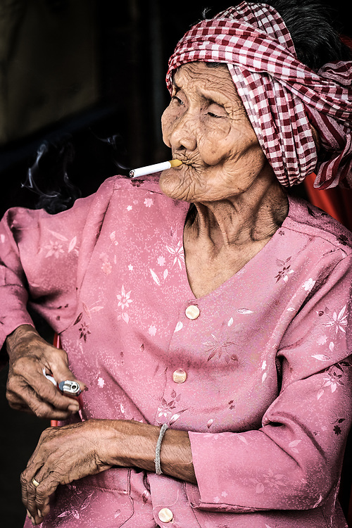 I photographed this Khmer woman out of the market in Kampot, Cambodia. It is very common in the country to see old women's smocking or chewing tobacco expecially in rural areas, while is still very unusual see young women's with cigarettes due to the bad reputation associated with it. <br /> Photo by Lorenz Berna