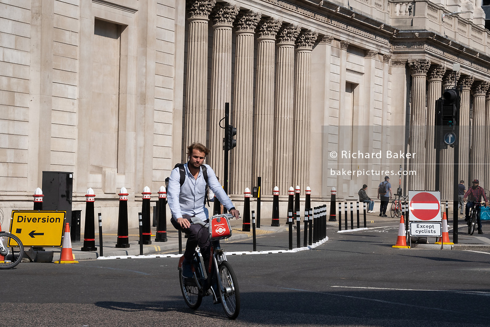 A male cyclist crosses the new layout of Threadneedle Street at Bank junction which has recently been altered to stop cars driving past the Bank of England during the Coronavirus pandemic - a time when office workers are still largely working from home, on 16th September 2020, in London, England.