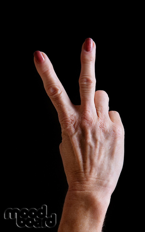 Senior woman's hands gesturing peace sign against black background