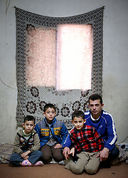 Syrian refugee Bassam Al Rahal, 30, with his sons (left to right) Ammar (5), Baker (10) and Omar (9). The family, which also includes Bassam's wife and daughter, live in an apartment in Tripoli, Lebanon, after fleeing their home in Homs, Syria.