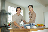 Young Couple husband standing wife sitting on bar in Kitchen portrait