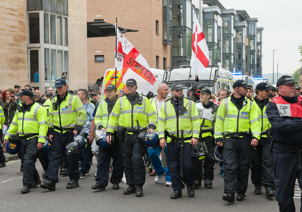 """© Licensed to London News Pictures.04/06/2016. Bristol, UK. Police escort a handful of anti-immigration protesters at protests in Bristol city  centre between the anti-immigration """"South West Infidels"""" and anti-fascist campaigners and Bristol Welcomes Refugees. There was  heavy police presence with dogs and horses, but only 18 anti-immigration protesters were escorted by police onto Bristol's College Green which was blocked off to the public by a ring of steel barriers. Photo credit: Simon Chapman/LNP"""