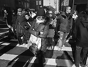 A group of shoppers crossing 56th Street and 5th Avenue in Midtown, New York City.
