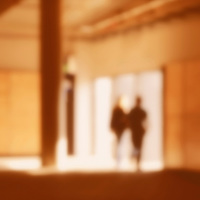 Two blurred persons leaving an orange brown and nearly empty room, they are walking towards the light