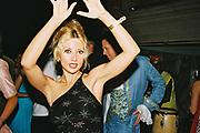 Woman on the dancefoor with hands in the air, in fornt of men wearing foppish costumes, Posh at Addington Palace, UK, August, 2004