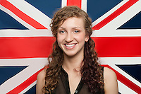 Portrait of happy young woman against British flag