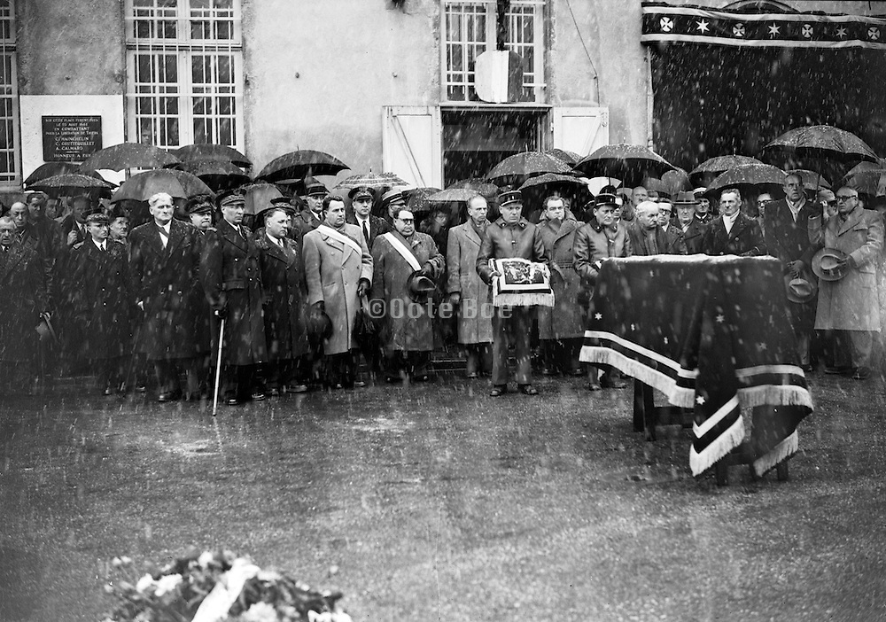 heavy rain downpour during a official funeral event with decoration display France 1940s