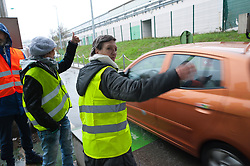 © Licensed to London News Pictures. 23/11/2018. Alby-sur-Chéran, Auvergne-Rhône-Alpes, France. Protesters secure motorway toll gate and allow motorists toll-free exit. Activists of the 'Gilet Jaune' national protest movement take part in 'Operation Paiement Gratuit' (free motorway) at an exit of the A41 motorway near Alby-sur-Chéran in the Auvergne-Rhône-Alpes region of France. The 'Gilet Jaune' campaign is against oppressive taxation, in particular motoring taxes on fuel etc. The name for their protest comes from the yellow Hi-Vis security waistcoat which French motorists are required to carry in vehicles by law. Photo credit: Graham M. Lawrence/LNP