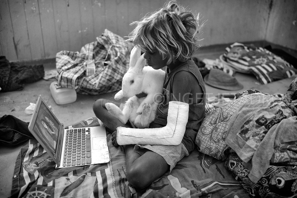 Quillan cuddles with a perfectly white rabbit while<br />