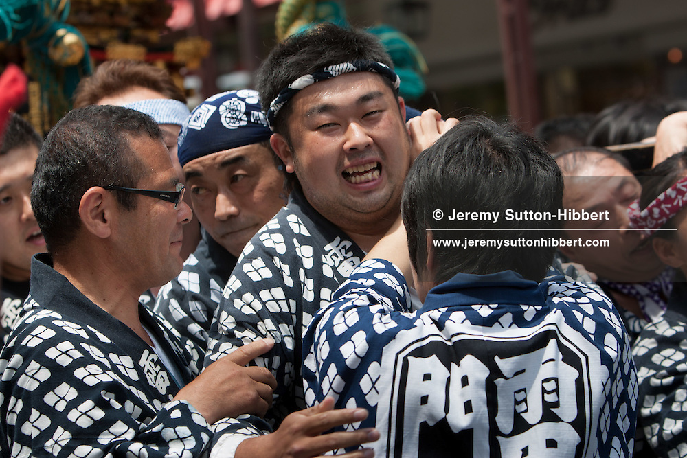 Local residents carry their mikoshi portable shrines through the streets of Asakusa district, on the 3rd day of the Sanja festival, in Tokyo, Japan, Sunday May 20th 2012.