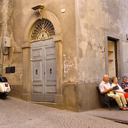People sit on bench in piazza around corner from Vespa scooter parked on cobblestone street with gated courtyard beyond, Orvieto, Umbria, Italy