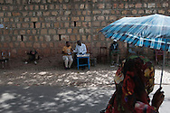 A woman using an umbrella to shield herself from the sun walks past a man conducting business on the streets of New Harar, just outside of the ancient city walls of Harar, Ethiopia.