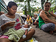 "07 AUGUST 2014 - BANGKOK, THAILAND:     A woman and her child wait for food distribution to start at Pek Leng Keng Mangkorn Khiew Shrine. Thousands of people lined up for food distribution at the Pek Leng Keng Mangkorn Khiew Shrine in the Khlong Toei section of Bangkok Thursday. Khlong Toei is one of the poorest sections of Bangkok. The seventh month of the Chinese Lunar calendar is called ""Ghost Month"" during which ghosts and spirits, including those of the deceased ancestors, come out from the lower realm. It is common for Chinese people to make merit during the month by burning ""hell money"" and presenting food to the ghosts. At Chinese temples in Thailand, it is also customary to give food to the poorer people in the community.  PHOTO BY JACK KURTZ"