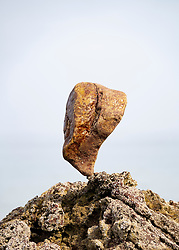 Single large stone balanced on rocks