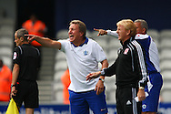 Loftus Road, London - Saturday 11th September 2010: Neil Warnock, manager of QPR shouts at his players with Gordon Strachan, manager of Middlesborough in the foreground during the Npower Championship match between Queens Park Rangers and Middlesborough. (Photo by Andrew Tobin/Focus Images)