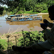 Bolivia. Copacobana. A man eats his lunch as a cargo ferry passed by on the Ibare river.