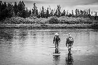 Two fly fisherman wade carefully across the Henry's Fork River in Idaho looking for the next rising fish.