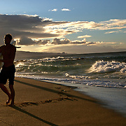 A surfer leaves the water near Honokua Bay in Maui, Hawaii.  The north shore of Maui is a popular surfing spot.