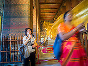 15 OCTOBER 2014 - BANGKOK, THAILAND: A European tourist looks the Reclining Buddha in Wat Pho in Bangkok while a tourist from India walks past. The number of tourists arriving in Thailand in July fell 10.9 per cent from a year earlier, according to data from the Department of Tourism. The drop in arrivals is being blamed on continued uncertainty about Thailand's political situation. The tourist sector accounts for about 10 per cent of the Thai economy and suffered its biggest drop in visitors in June - the first full month after the army took power on May 22. Arrivals for the year to date are down 10.7% over the same period last year.   PHOTO BY JACK KURTZ