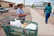 07 AUGUST 2005 - PHOENIX, AZ: YSIDRO, who lives on the streets of Phoenix, AZ, smokes a hand rolled cigarette while he watches his belongings in a shopping cart before a church service for street people in downtown Phoenix. The service is performed by ministers from Agape Harvest Church, which holds weekly church services for street people in Phoenix. They also hand out water and food and distribute clothes. They have been involved in the street ministry for about six months. About 50 people usually attend the service and meals.  PHOTO BY JACK KURTZ