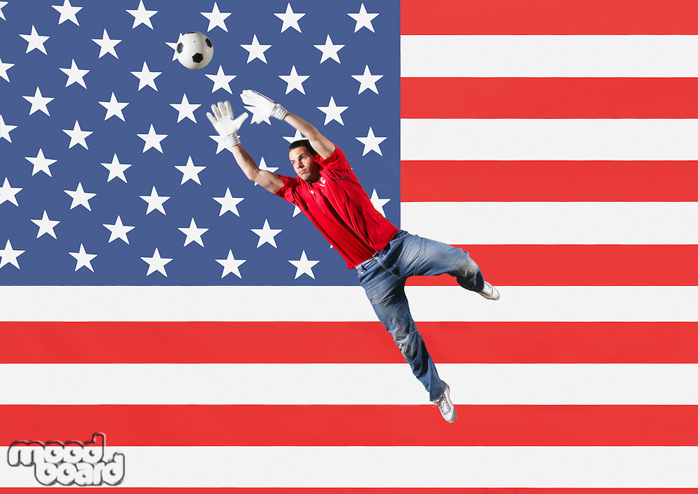 Goalkeeper saving ball in front of Brazilian flag