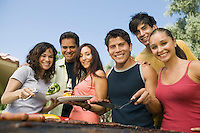 Group of young people around outdoor grill portrait