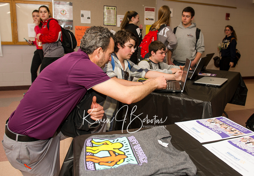 """Special Education teacher Alex Takantjas helps Carter Dutton and Jake Deware sign up for the """"Best Buddies"""" program at Belmont High School Thursday morning.  (Karen Bobotas/for the Laconia Daily Sun)"""
