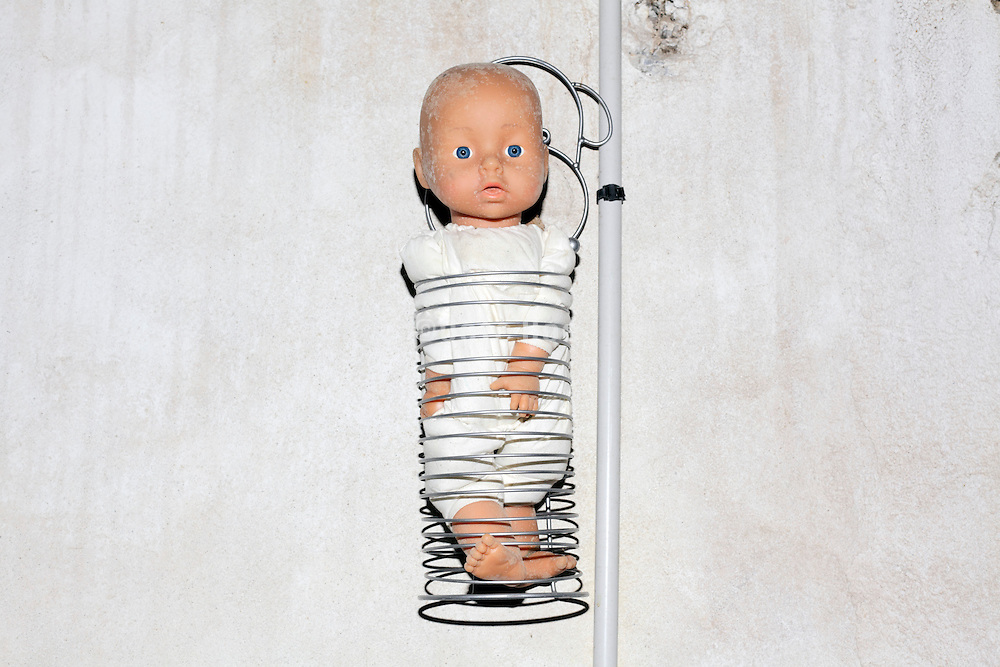baby doll confined in metal coil