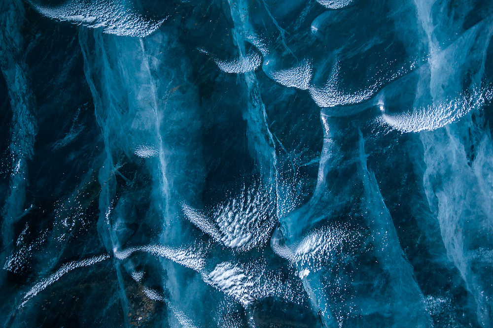 Snow dusts melt cups on exposed glacier ice on Rabotbreen, Svalbard. Cracks and air bubbles form complex structures inside the ice.