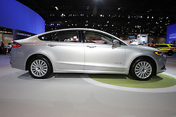 08  February 2013: 2013 Ford Fusion Hybrid 5 passenger 2.0L IVCT HEV automobile. Chicago Auto Show, Chicago Automobile Trade Association (CATA), McCormick Place, Chicago Illinois<br /> <br /> 2013 FORD FUSION: All-new, the 2013 Ford Fusion is a stand out in today's competitive midsize car market, with sweeping lines that symbolize the next generation sedan from FoMoCo. Available in three distinct models - S, SE and Titanium, Fusion offers the broadest selection of fuel-efficient powertrains in its segment. We're talking hybrid and plug-in hybrid alternatives, a pair of EcoBoost four-cylinder engines, a normally aspirated four-cylinder engine, and automatic start-stop technology to shut off the engine at stationary idle. Buyers have their selection of front-wheel or all-wheel drive applications, and a choice between automatic and manually shifted six-speed transmissions. Horsepower ratings range from 175 up to 240 hp. Topping the fuel-efficiency ladder is the Fusion Energi plug-in hybrid, aimed to deliver more than 100 MPGe, a mile per gallon equivalency metric for electrified vehicles. Inside, the new Fusion offers a sporty, driver-oriented environment with five-passenger seating, and a 16.0 cu. ft. trunk for luggage or groceries. Fusion is offered with the latest technologies, including Blind Spot Information System with cross-traffic alert, lane keeping technology, adaptive cruise control, active park assist, and voice control MyFord Touch system.
