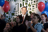 Students, staff and visitors watch the inauguration ceremonies near a cutout of the President Obama.