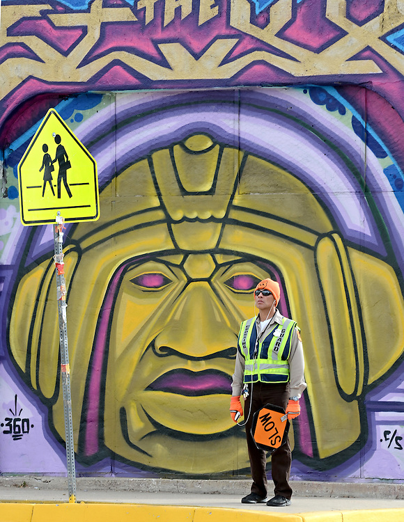 School crossing guard Conrad Lucero keeps watch on the corner of Edith and Coal as a mural keeps watch on him, photographed on Thursday, Jan. 30, 2014. (Dean Hanson/Albuquerque Journal)
