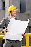 Young male engineer holding blueprint while looking away at construction site