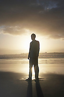 Silhouette of business man standing on beach against sunset
